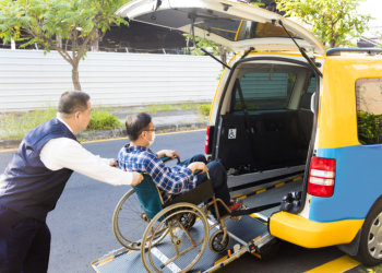 man pushing the wheelcair of the patient